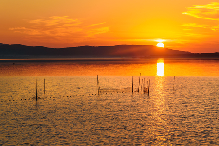 View sunrise in lagoon Orbetello on peninsula Argentario in Tuscany. Italy Imagens - 115664971
