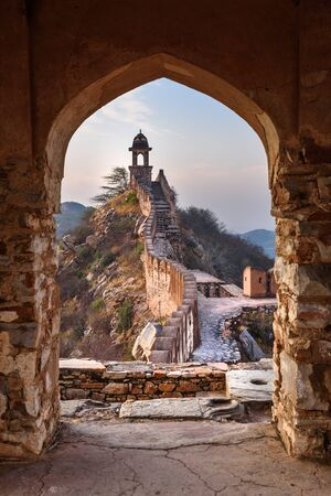 Ancient long wall with towers around Amber Fort through the arch of tower walls at morning. Jaipur. Rajasthan. India Stock Photo