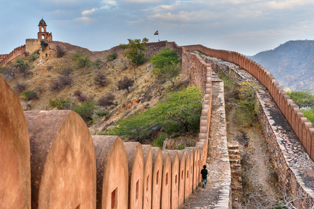 Ancient long wall with towers around Amber Fort at evening. Jaipur. Rajasthan. India