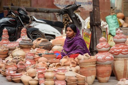 Bikaner, India - February 11, 2019: Indian woman selling clay pots on local market in Bikaner. Rajasthan