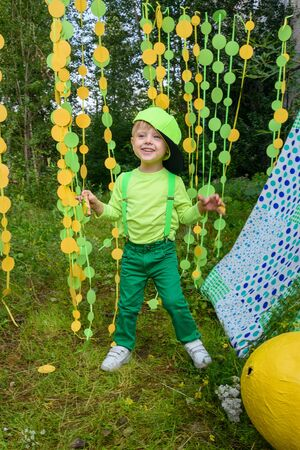 Little boy dancing on paper circle colorful curtain garland background in park in summer day Фото со стока