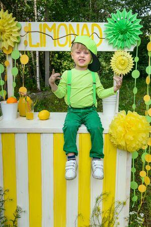Little boy sitting on lemonade stand in park in summer day