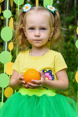 Girl with orange in paper circle colorful curtain garland in park