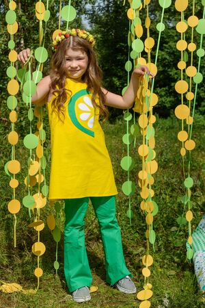 Young girl in paper circle colorful curtain garland in park Фото со стока - 130360469