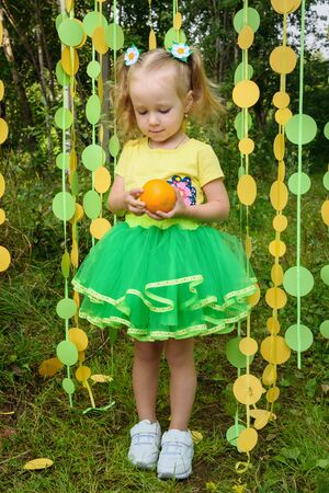 Girl with orange in paper circle colorful curtain garland in park Фото со стока - 130360472