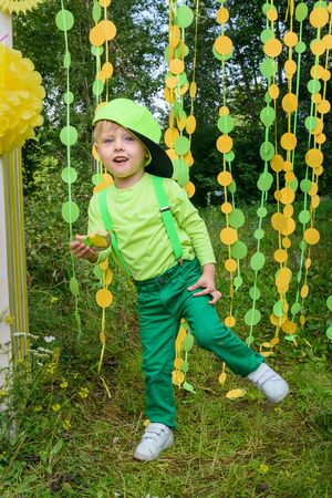 Little boy dancing on paper circle colorful curtain garland background in park in summer day Фото со стока - 130360475