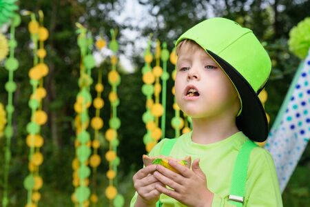 Little boy eating biscuit on colorful background in park in summer day Фото со стока - 130360484