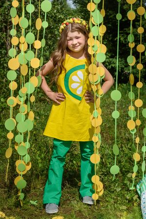 Young girl in paper circle colorful curtain garland in park Фото со стока - 130361161