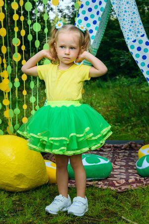 Little girl on colorful background in park in summer day