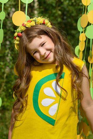 Young girl in paper circle colorful curtain garland in park