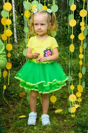 Girl in paper circle colorful curtain garland in park Фото со стока