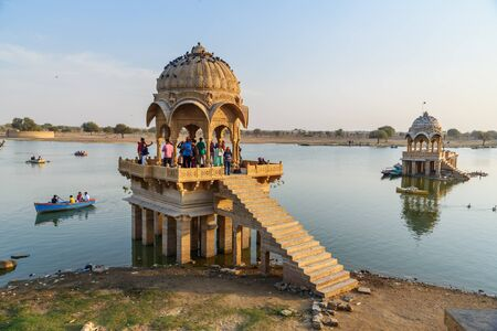 Jaisalmer, India - February 13, 2019: Gadisar lake, man-made water reservoir with temples in Jaisalmer. Rajasthan