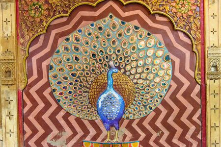 Jaisalmer, India - February 13, 2019: Peacock made of molten glass and mirrors on wall of Patwon ki Haveli palace in Jaisalmer. Rajasthan