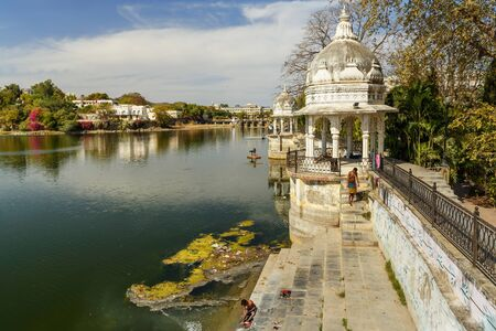 Udaipur, India - February 17, 2019: Walking Track park on Swaroop Sagar Lake is artificially created lake. It combined water body comprising other nearby lakes Fateh Sagar Lake and Lake Pichola