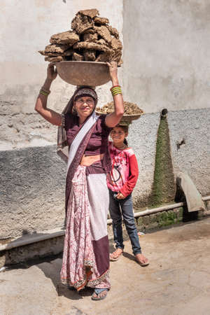 Nandgaon, Uttar Pradesh , India - March 22, 2019: Indian woman and girl carrying basin with cow dung cakes on their heads