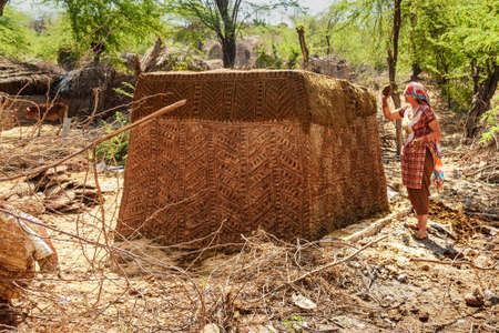 Nandgaon, Uttar Pradesh , India - March 22, 2019: Indian woman moldes small hut that are built to store cow or buffalo dung that will be used later as traditional cooking fuel on hearths Sajtókép
