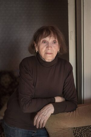 Senior woman of 70 years old standing by the couch at home