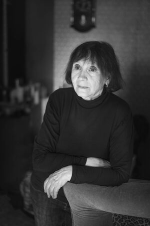 Senior woman of 70 years old standing by the couch at home. Black and white portrait