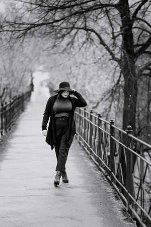 Brunette girl in hat on the bridge in cit in autumn .. Plus size model. Black and white Stock fotó