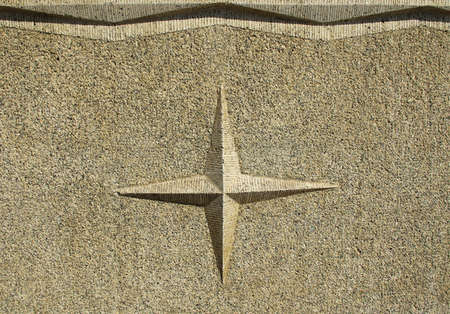 Convex four-pointed star on a sandstone wall