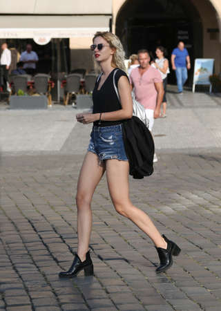 A young slender blonde girl in a black T-shirt and blue denim shorts walks through the square in Prague.