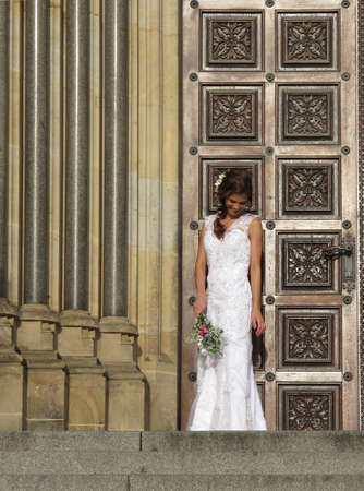 A full-length portrait of a smiling bride in a long wedding dress holding a bouquet at the entrance to the Church of St. Ludmila.