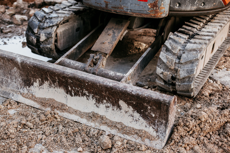 Close up of bulldozer or excavator working with soil on construction site. Reklamní fotografie