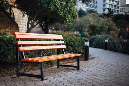 Empty orange bench in public park opposite residential area