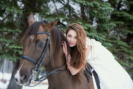 Image of a girl in a white dress on a horse photo