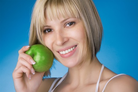 Image of a smiling girl with a green apple on a blue background. photo