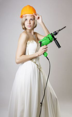 Picture of a girl in evening dress with a drill in the hands of photo