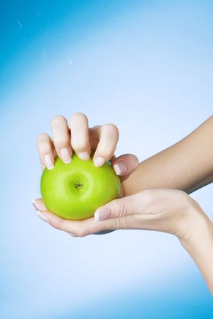 seized: Picture of a girl who seized nails the green apple on a blue background Stock Photo