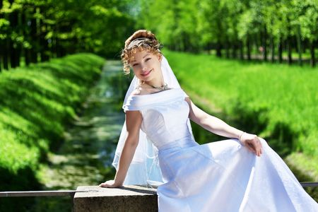 Picture of beautiful curly bride in the park. photo