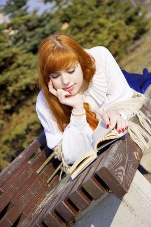 L'image d'une jeune fille qui lit le livre dans le parc sur un banc dans une journée ensoleillée Banque d'images - 4708137