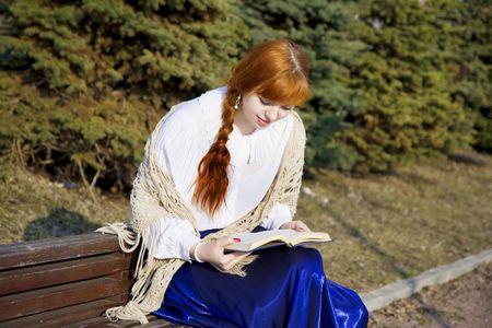 L'image d'une jeune fille qui lit le livre dans le parc sur un banc dans une journée ensoleillée Banque d'images - 4708135