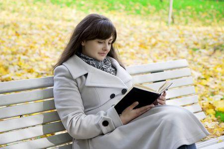 Photo d'une jeune fille qui lit le livre dans le parc sur un banc Banque d'images - 4707907