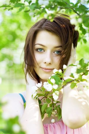 The image of the beautiful girl in the garden among the blooming trees photo
