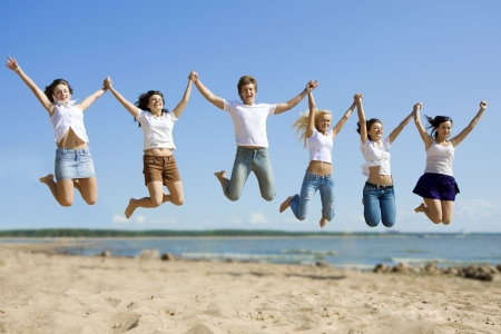 friends party: The image of a group of friends that are jumping on the beach