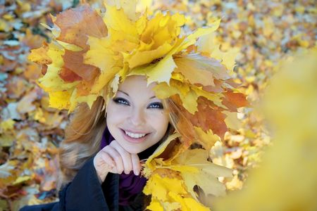 Images of a beautiful girl in the autumn wreath of maple leaves photo