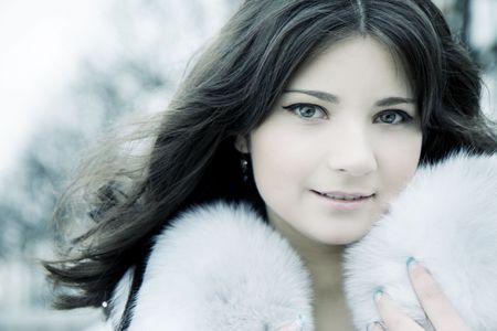 woman in fur coat: The image of a beautiful girl in the background of a winter city Stock Photo
