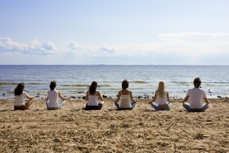 team lotus: Image of a group of people sitting on the beach Stock Photo
