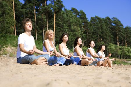 Image of a group of people sitting on the beach photo