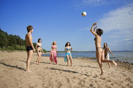 Image of people on the beach playing volleyball photo