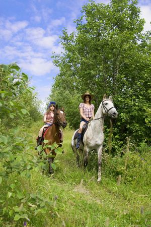 Image of two girls ride horses in the park photo