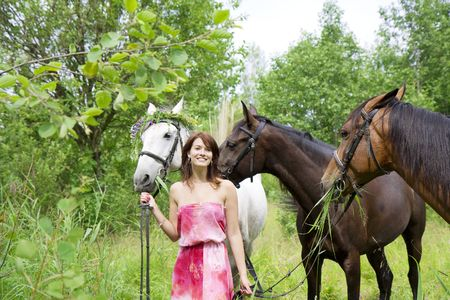 The image of a beautiful brunette girl with horses photo