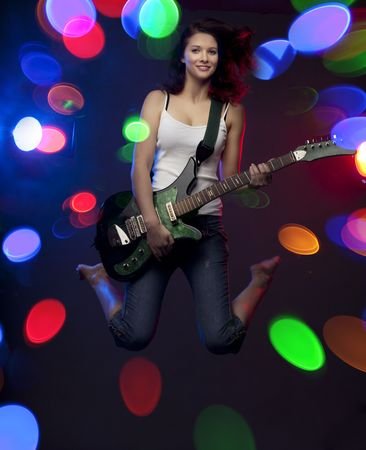 Image of a beautiful girl with a guitar in the spotlight photo