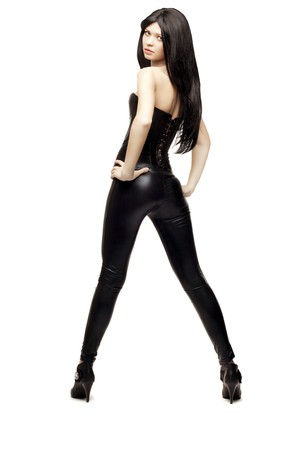 Images of an amazing girl in black leather pants and corset on a white background Stock Photo - 7623312