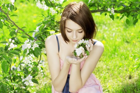 The image of a beautiful girl on a background of flowering trees photo