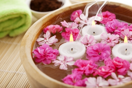 spa therapy: Image of spa therapy, flowers in water, on a bamboo mat.