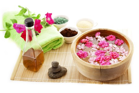 spa resort: Image of spa therapy, flowers in water, on a bamboo mat.
